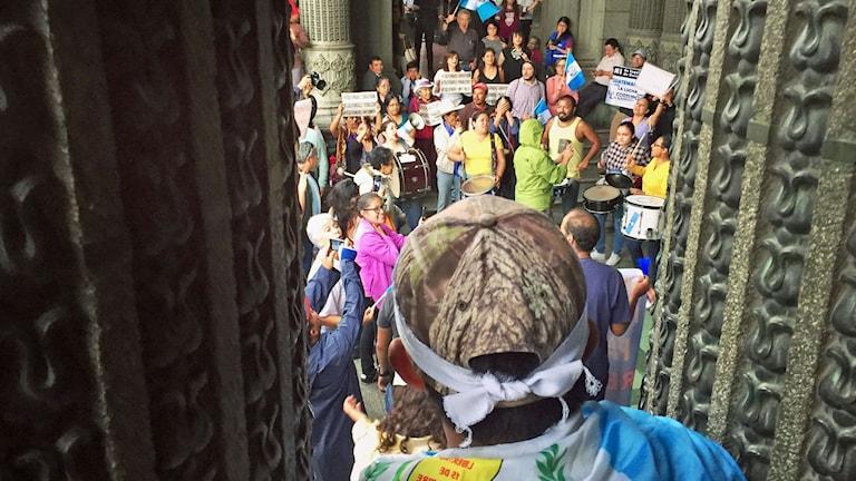 En pojke tittar ner på demonstranterna som samlats utanför presidentpalatset i Guatemala.