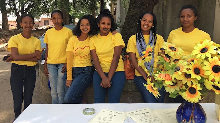 Sex kvinnor iklädda gula tröjor står vid ett bord.