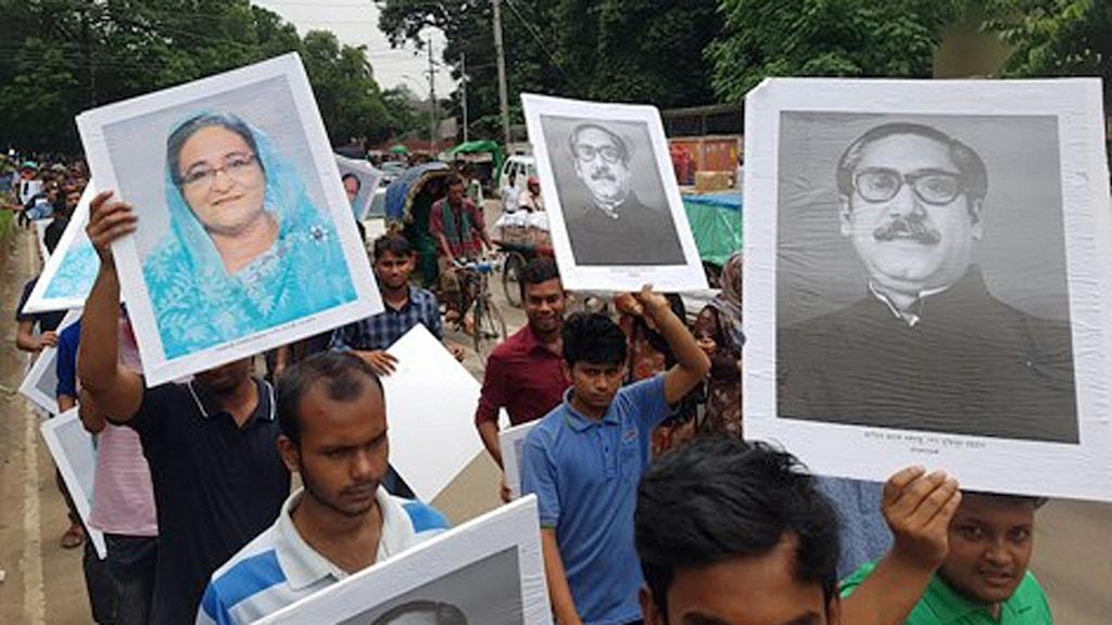 Studenter från Bangladesh Chatra League håller upp bilder på premiärminister Sheikh Hasina och hennes far, Sheikh Mujibur Rahman.