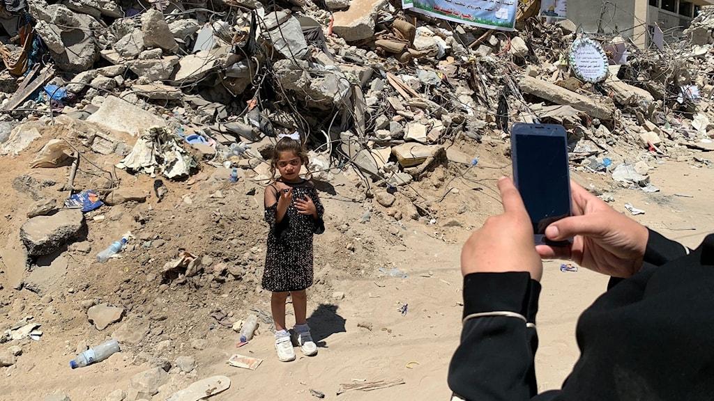 En mamma fotar sin femåriga dotter  utanför de hem där 42 människor dödades.