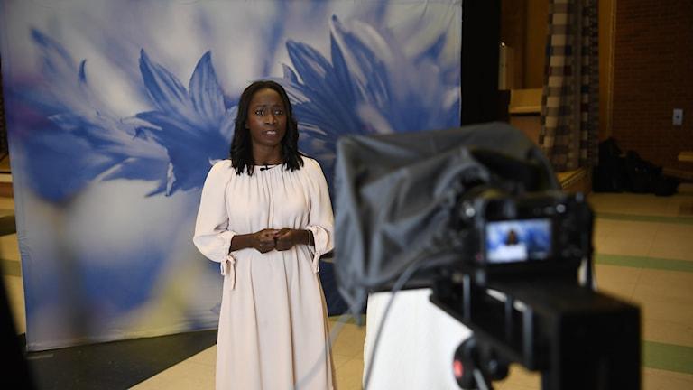 Kvinna i vit klänning står framför en kamera och pratar mot en blåblommig bakgrund.