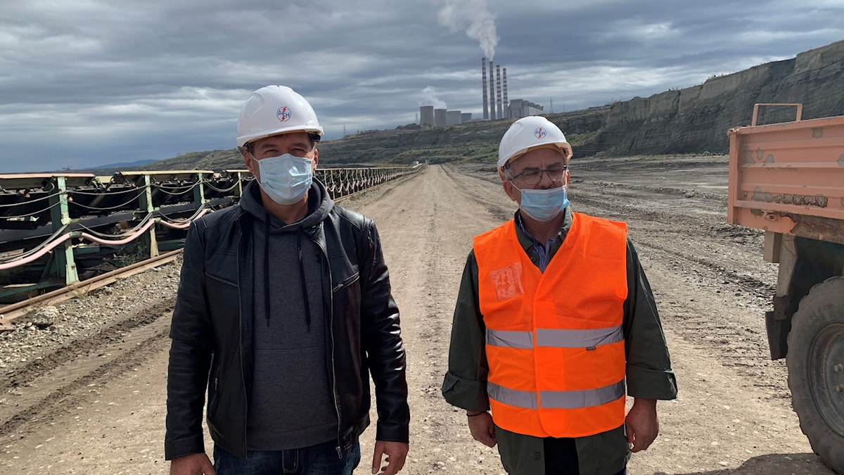 Två män som står vid en kolgruva. En i svart jacka och den andra i orangea skyddsväst. Båda bär masker och skyddshjälm.