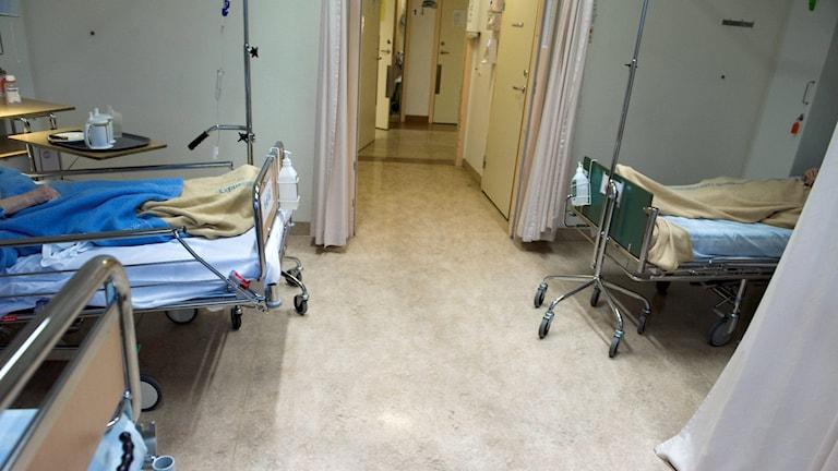 Bild på två sjukhussängar som står mittemot varandra i en sal.