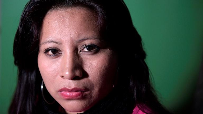 En kvinna med mörkt hår tittar in i kameran.