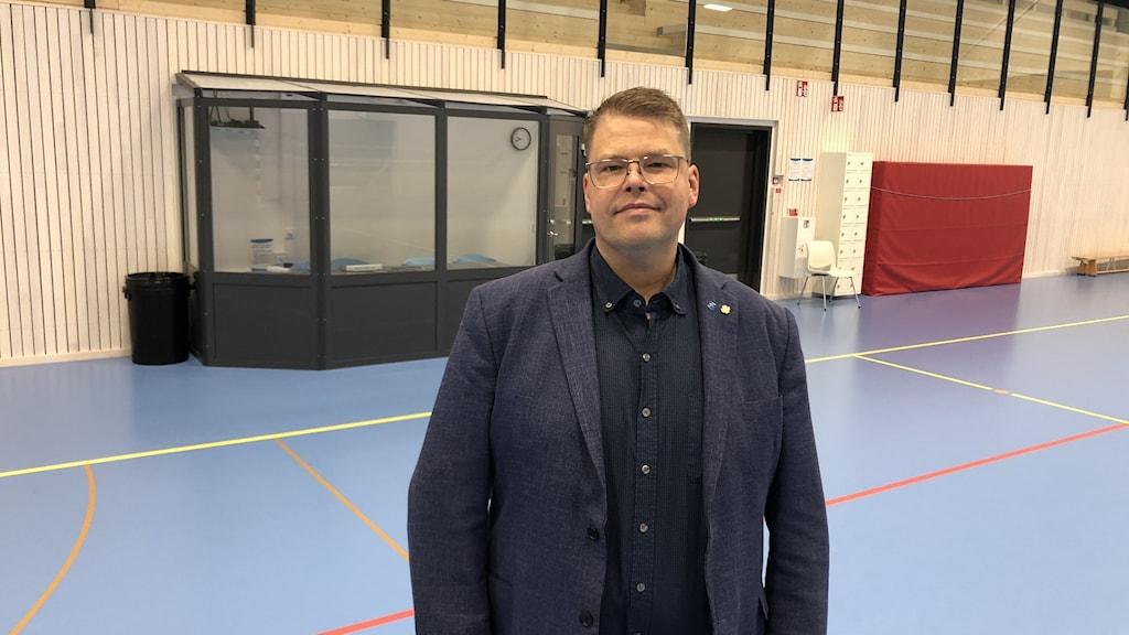 Man i svart skjorta, blå kavaj och glasögon står inne i en gymnastikhall.