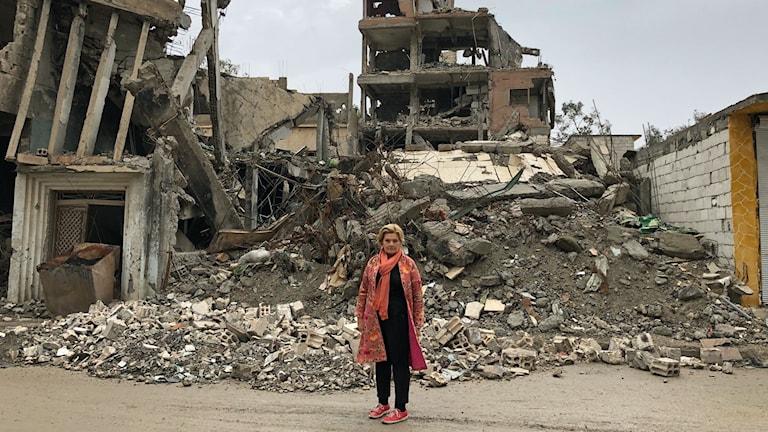 Vår korrespondent Cecilia Uddén framför ruiner i Raqqa.