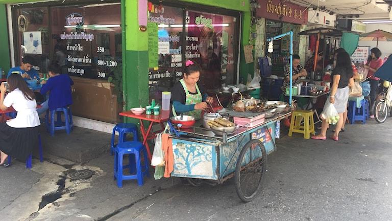 Kvinna vid en matvagn i ett gatuhörn