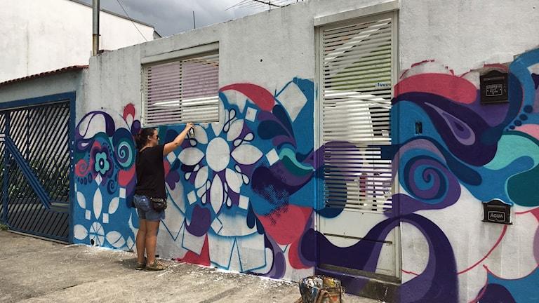 Barbara Goy målar graffiti på en husvägg