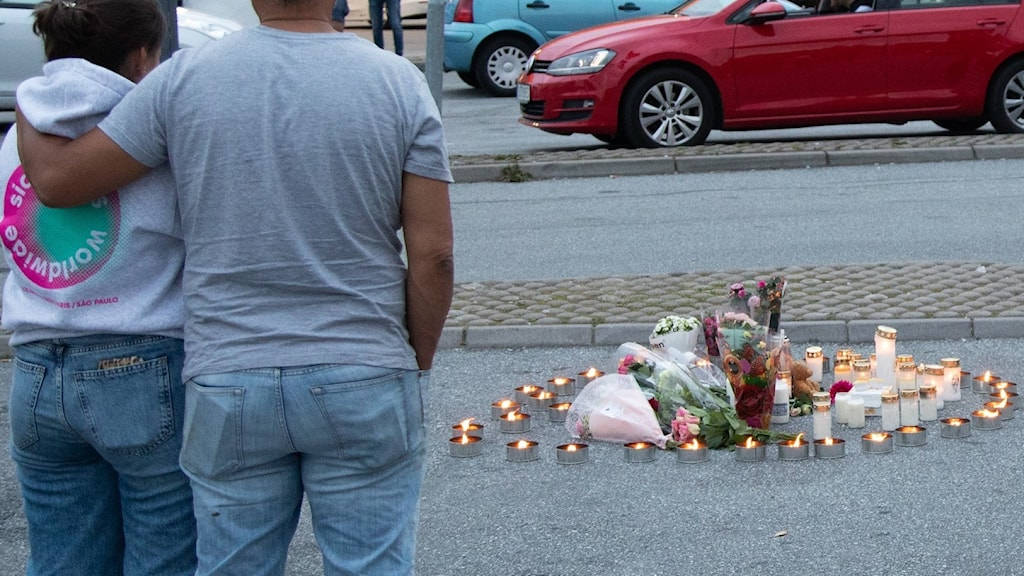 Blomor och ljus på platsen där en tolvårig flicka sköts till döds vid en bensinmack i Norsborg i Botkyrka.