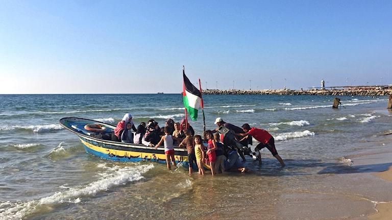 Exteriör: en liten båt vid stranden på väg ut på vattnet, fylld med barn och några vuxna. Palestinaflagga. Gaza