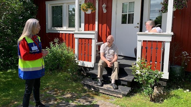 Äldre par sitter på farstutrappan. Volontär på besök.