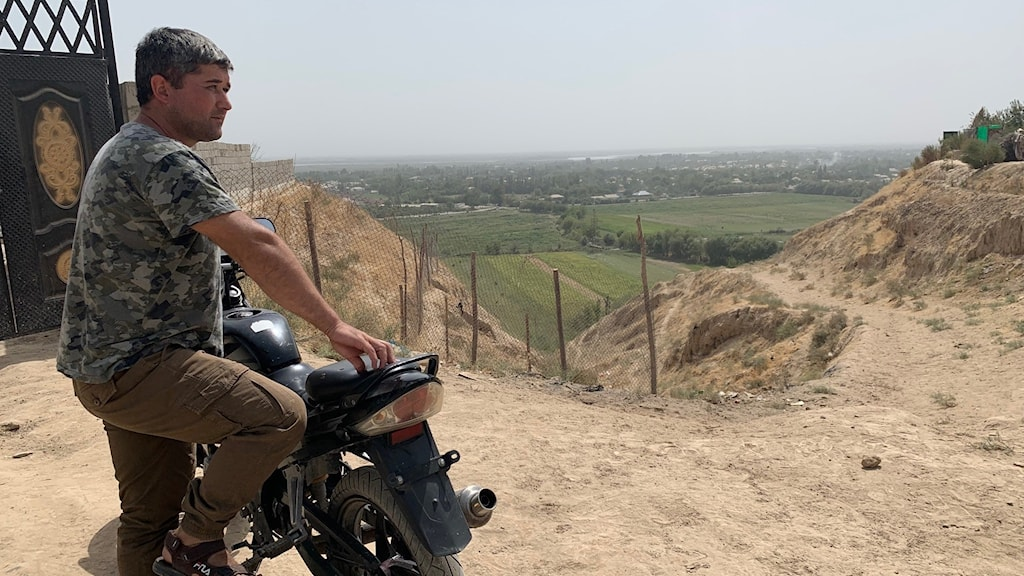 Man står bredvid en motorcykel och blickar ut över en dal.