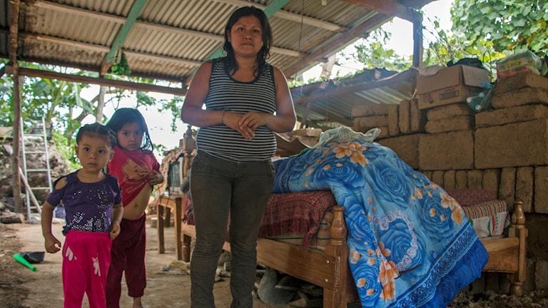 En kvinna står under ett tak med två barn