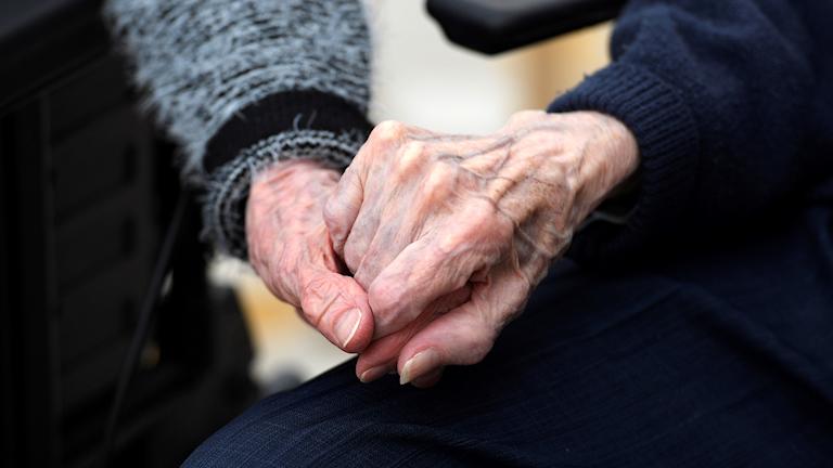 Äldre håller hand.