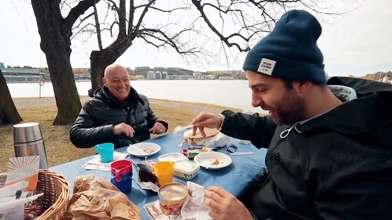 Vladmir Pozner tillsammans med kollegan Ivan Urgant luktar på surströmming i dokumentären om Sverige och Norden.