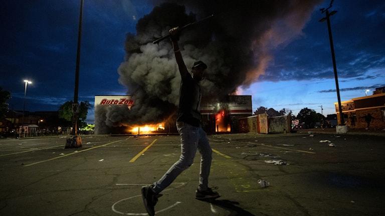 Butik i brand och framför den en person som sträcker upp höger arm i luften.