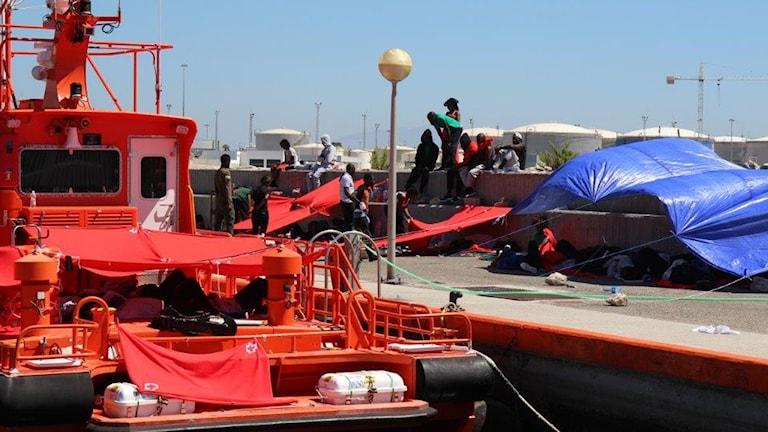 Spanska sjöräddningens båtar, migranterna har spänt upp presenning som solskydd.