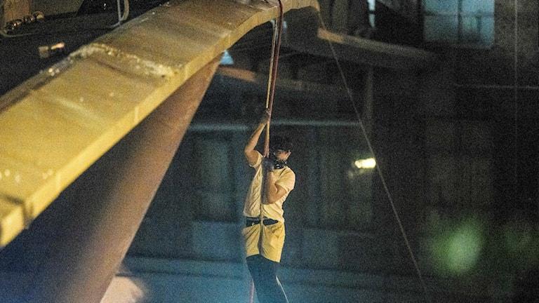 Student klättrar ner med hjälp av rep från en bro.