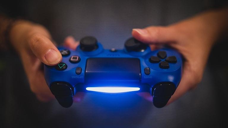 Händer som håller i en tv-spelskontroll