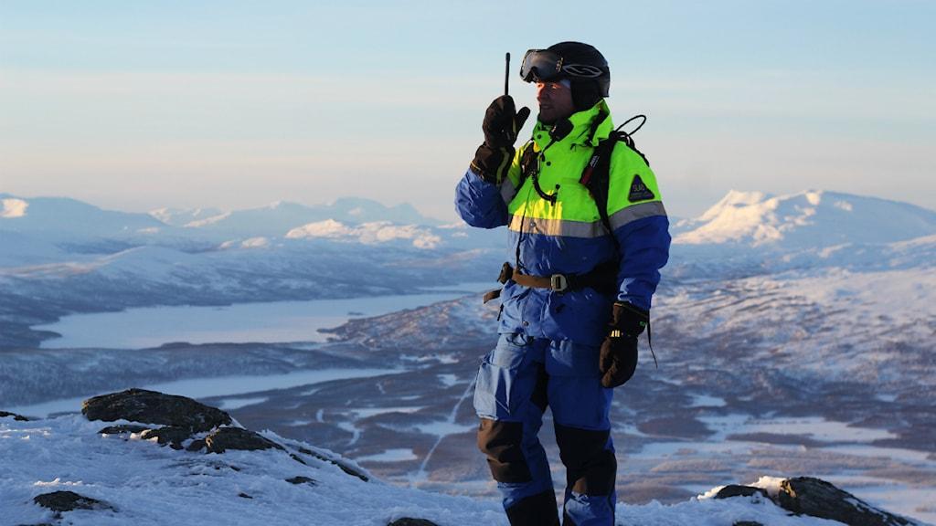 Fjällräddaren Johan af Ekenstam testar sin polisradio på en fjälltopp i Hemavan. Till vardags jobbar han som pistör i skidbackarna och har då inte på sig fjällräddarnas uniform. Foto: David Carr/Sveriges Radio.