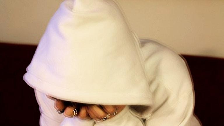 kvinna sitter på säng och döljer ansiktet i händerna.