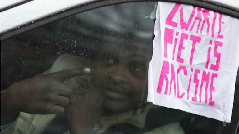 """En taxichaufför har hängt ut en skylt som säger """"Svarte Petter är rasism"""", under Sinterklaasfirandet i Amsterdan 2014. Foto: Peter Dejong/TT"""