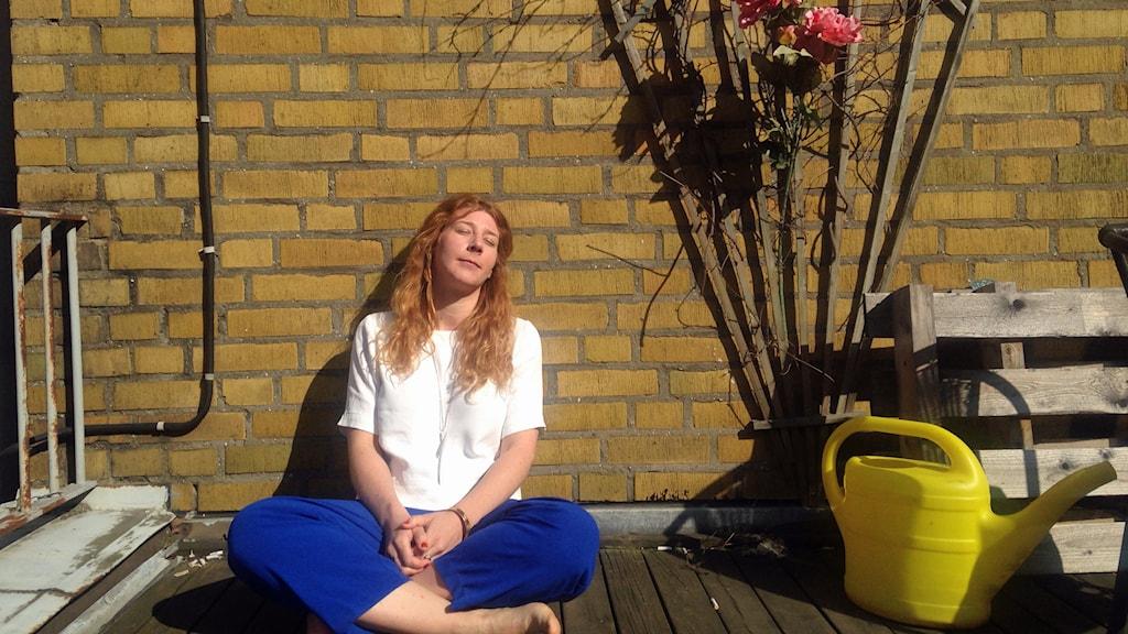 kvinna som mediterar på en altan