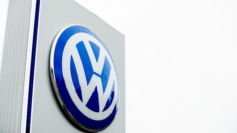 Bild på Volkswagens logotyp på en grå pelare.