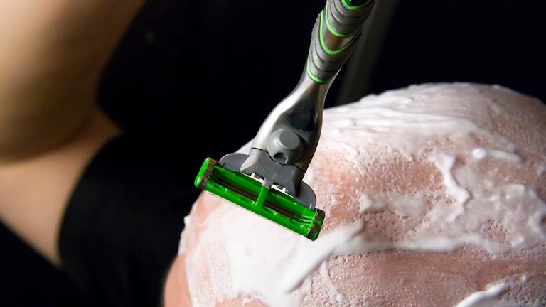 Bild på person som rakar sitt huvud med en rakhyvel.