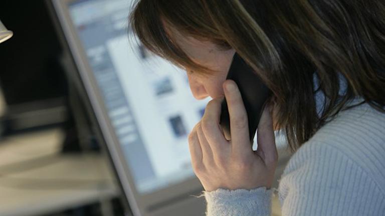 Tjej som pratar i telefon framför en dator