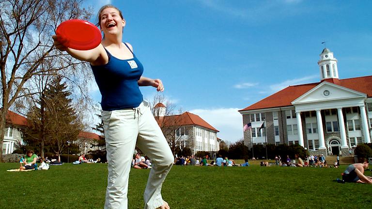 Bild på en tjej som kastar en röd frisbee på en äng