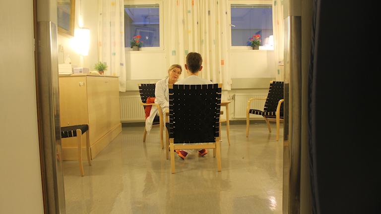 Bild på en sjuksköterska som sitter och pratar med en patient i ett väntrum.