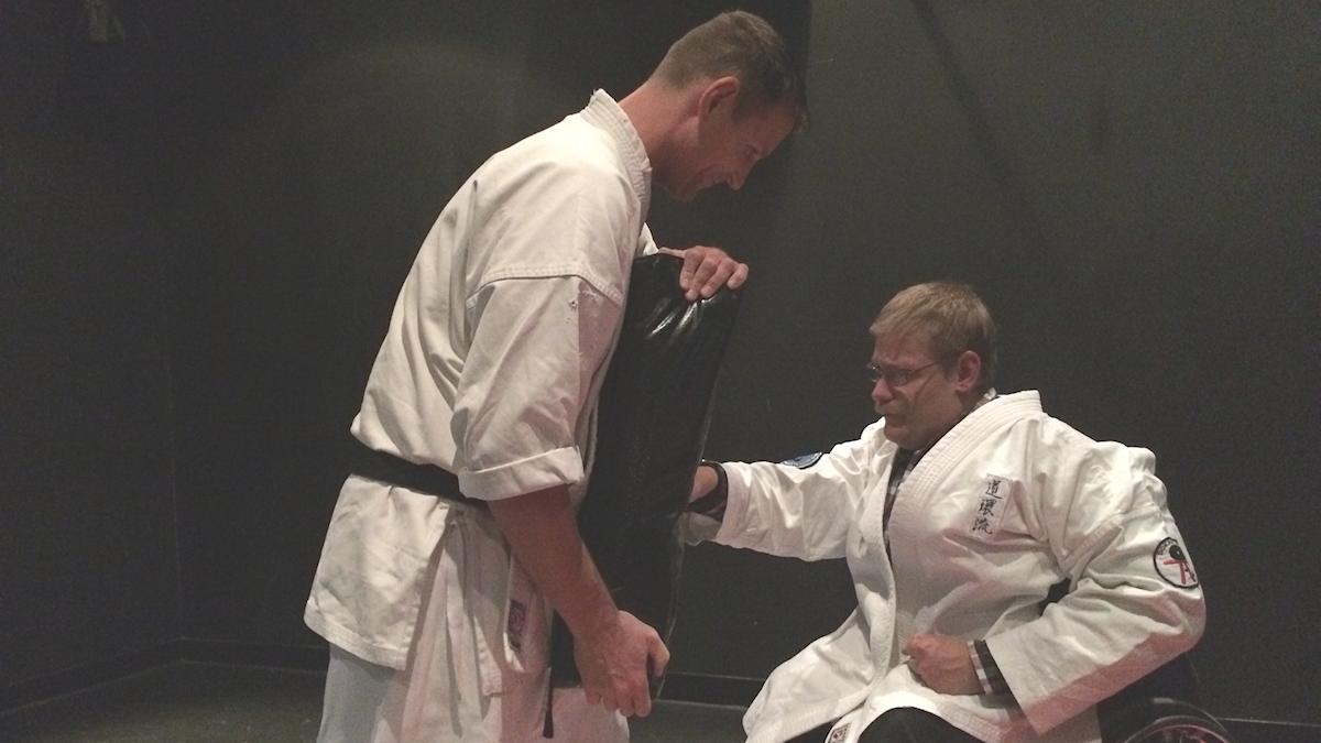 Två personer som tränar självförsvar. En av personerna sitter i rullstol och slår mot en man som står upp.