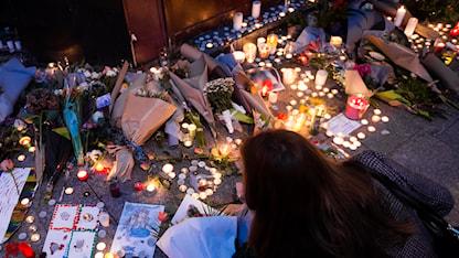 En kvinna lägger blommor utanför restaurangen Le Carillon i Paris lördagen efter terrorattacken