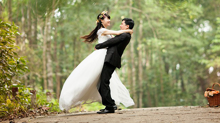 Bild på ett par i bröllopskläder som lyfter upp varandra. Foto: Pixabay