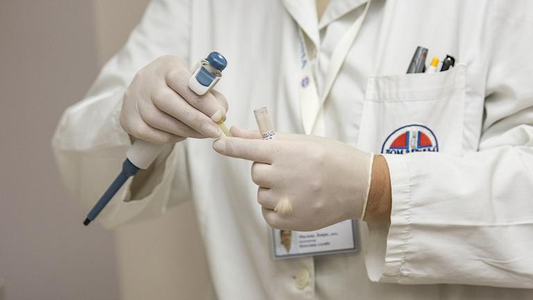 Bild på en person i sjukhuskläder som håller i ett provrör.