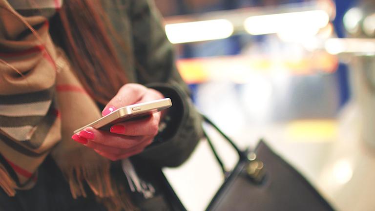 Bild på en tjej som håller i sin smartphone. Foto: Pixabay