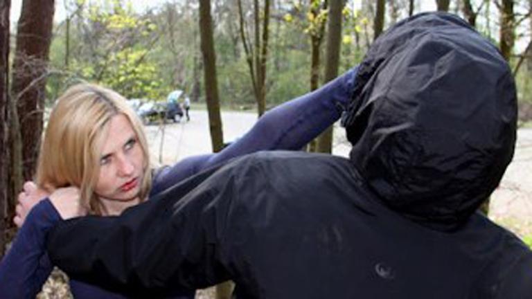 Bild på en blond tjej som petar en man med svart luva i ögonen. Foto: