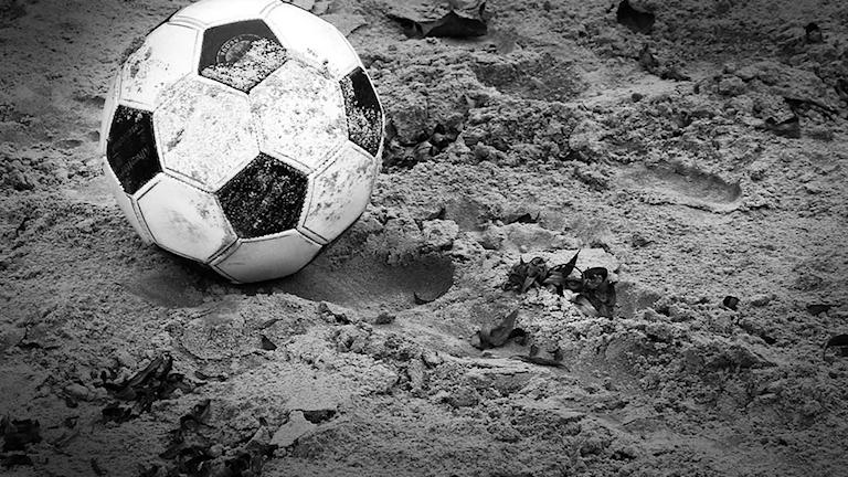 Svartvit bild på fotboll i sand.