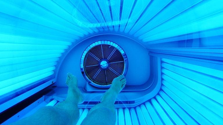 Bild på fötter i ett solarium med blått ljus.