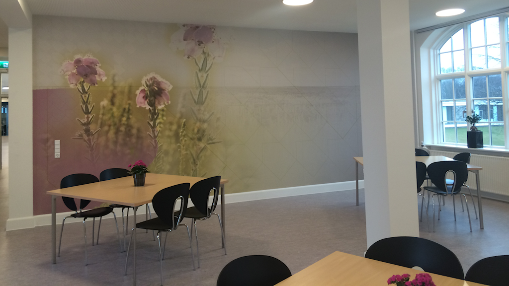 Lavendelfärgade blommor på väggen i kafeterian, taget av en fotograf i något av områdena avdelningens patienter kommer ifrån. Foto: Palmira Koukkari Mbenga/Sveriges Radio