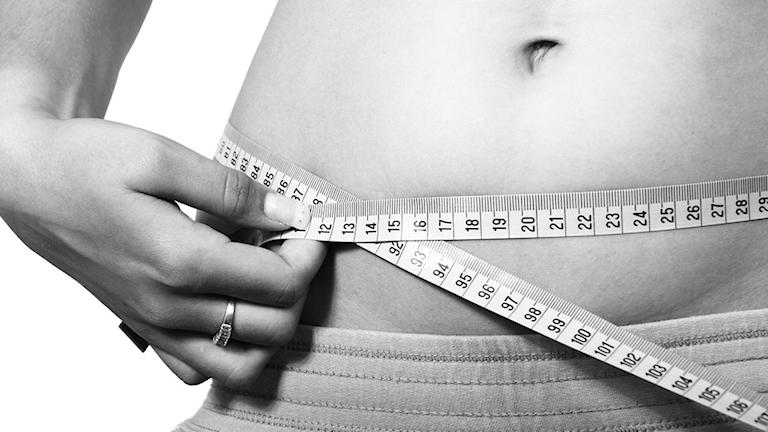 Bild på en person som mäter sin midja med ett måttband