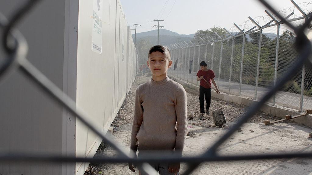 En kille bakom stängslet på det låsta förvaret på ön Chios i Grekland