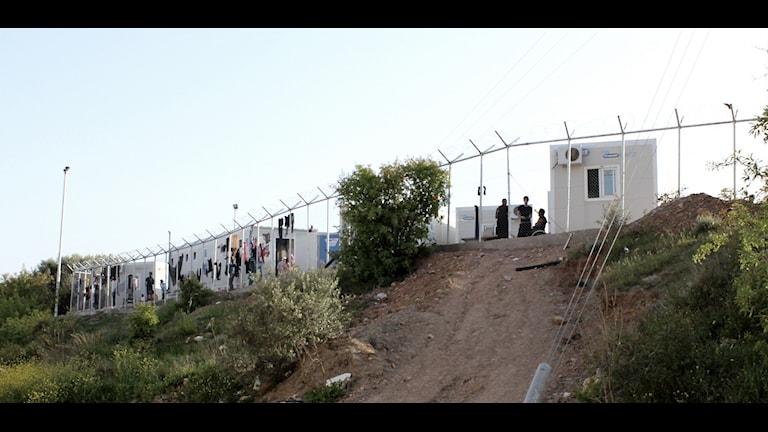Kuvassa näkyy korkean aittauksen takana sijaitseva pakolaisleiri Kreikassa.