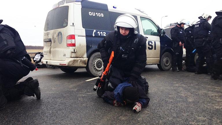 En polis håller fast en aktivist genom att trycka honom ner mot marken.