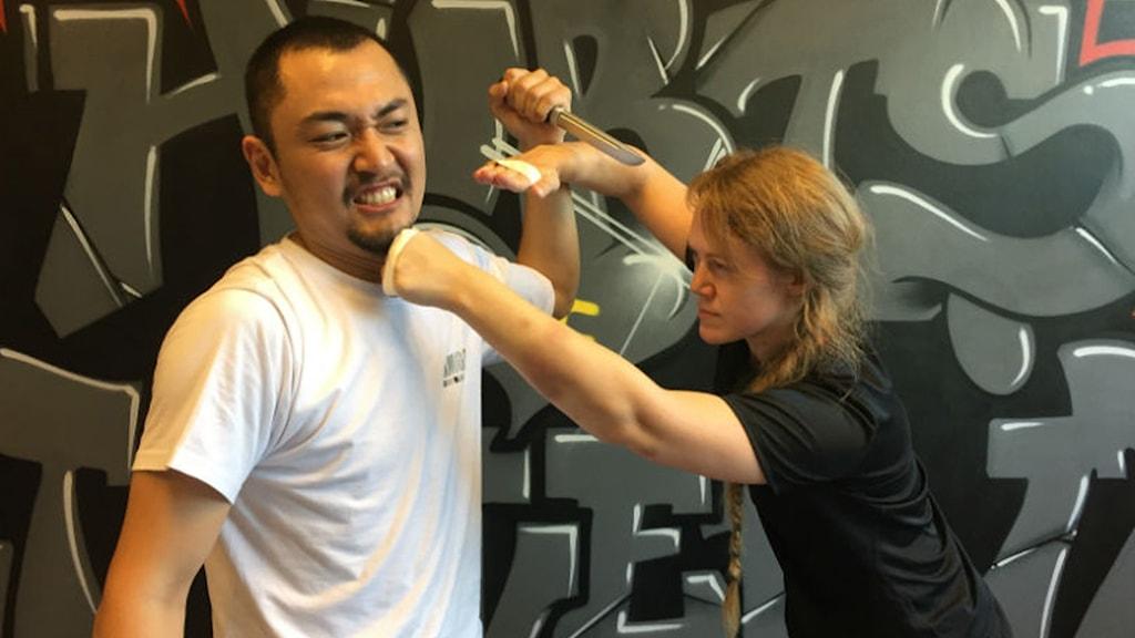 Emma Dalman som är krav maga-instruktör låtsas slå en kille med en kniv i handen.