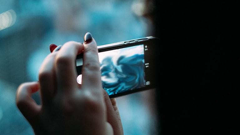 Bild på en mobiltelefon & person som filmar med den.