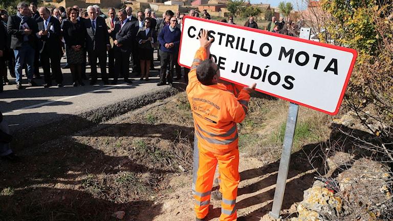 Bild på en vägarbetare som sätter upp en skylt med namnet Castrillo Mota de Judíos