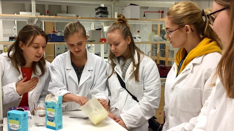 Fem teknikstudenter experimenterar i ett labb