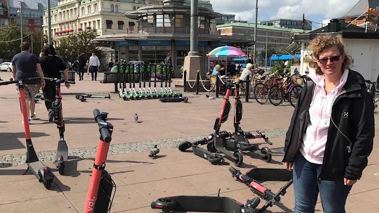 Kvinna och välta sparkcyklar på torg